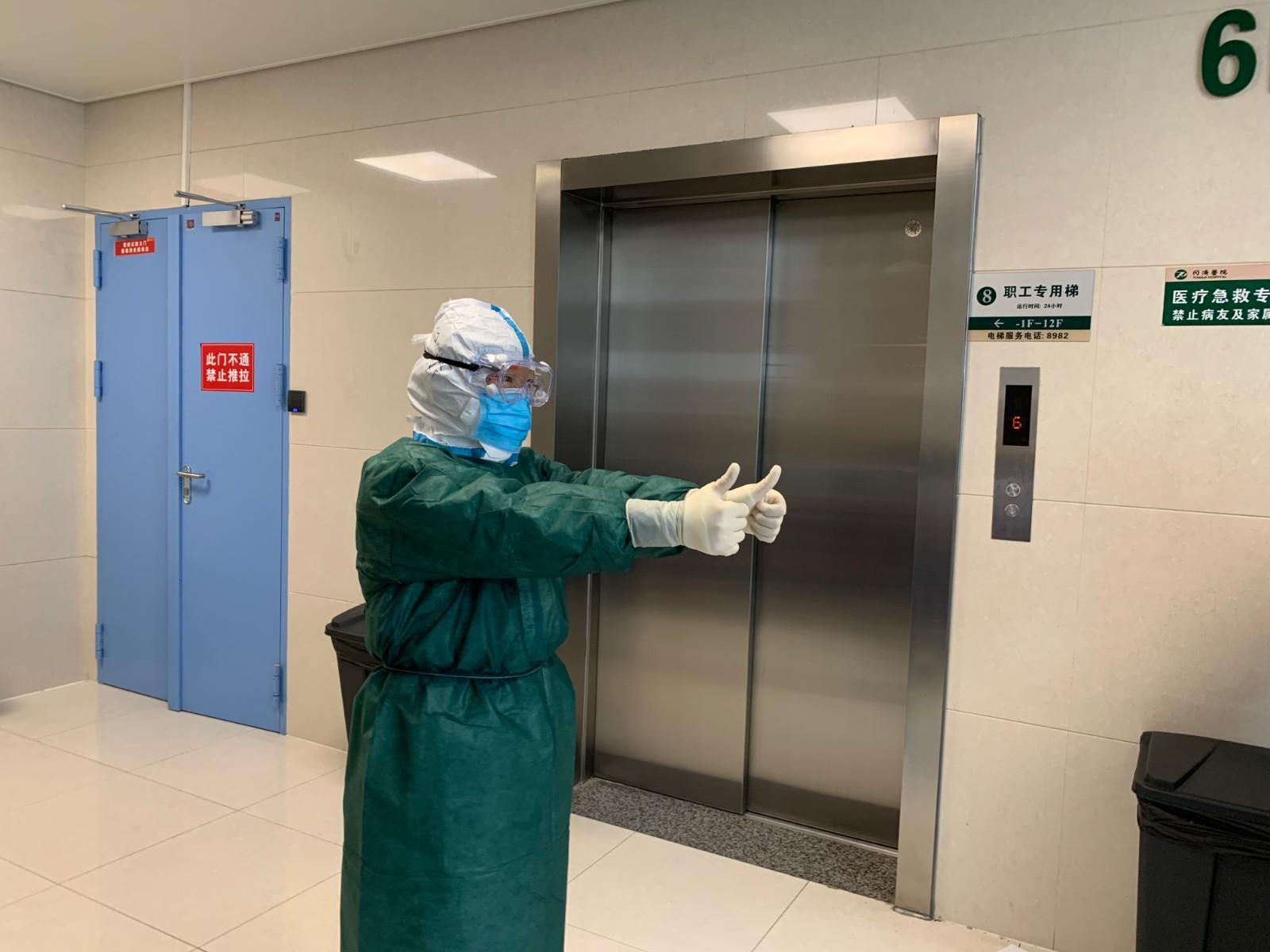 2月21日,华中科技大学同济医学院附属同济医院中法新城院区,一位即将进入新冠肺炎隔离病房的北京中日友好医院的医护人员在摄影师的镜头前做出点赞的手势。.JPG